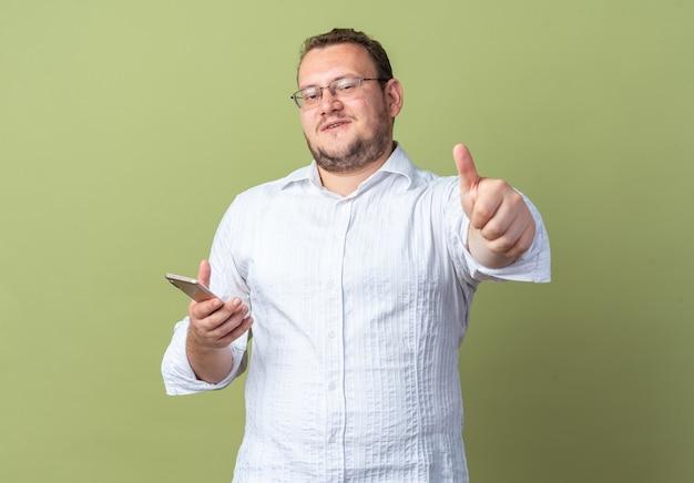 안경을 쓴 흰색 셔츠를 입은 남자가 스마트폰을 들고 앞을 바라보며 녹색 벽 위에 엄지손가락을 들고 즐겁게 웃고 있습니다.