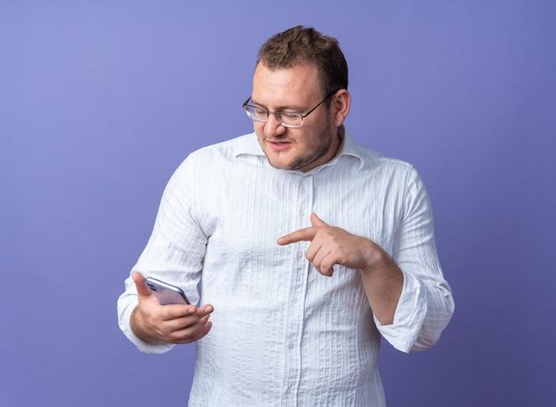 青い壁の上に立って混乱している人差し指でそれを指しているスマートフォンを保持している眼鏡をかけている白いシャツの男