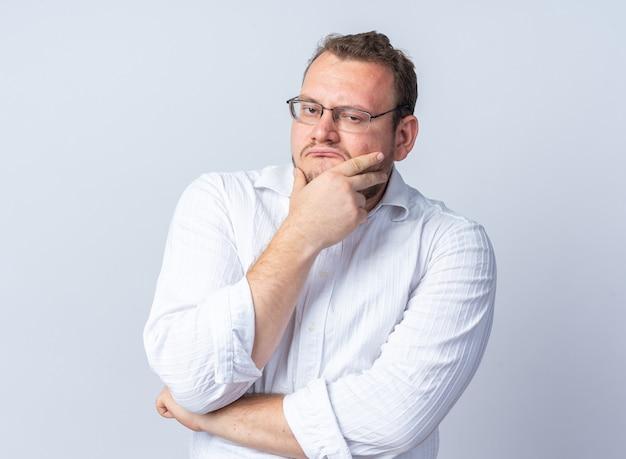 안경을 쓴 흰 셔츠를 입은 남자가 흰 벽 위에 서 있는 얼굴에 슬픈 표정으로 정면을 바라보고 있다