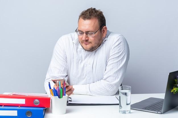 피곤하고 지루해 보이는 안경을 쓴 흰 셔츠를 입은 남자가 사무실에서 일하는 흰 벽 위에 노트북 사무실 폴더와 클립보드를 들고 테이블에 앉아 있다