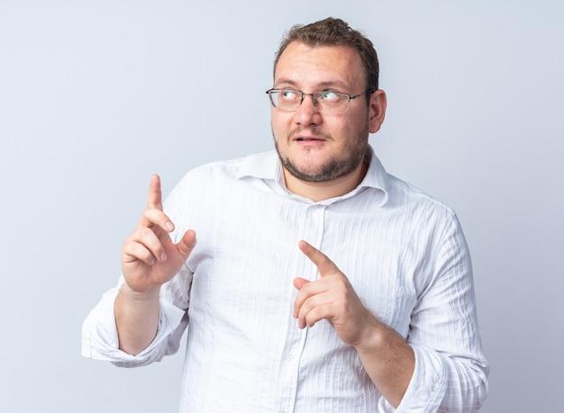 안경을 쓴 흰 셔츠를 입은 남자가 흰 벽 위에 서 있는 검지 손가락으로 행복하고 긍정적인 방향을 바라보고 있다