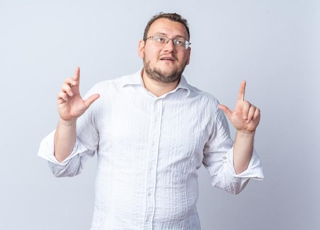 Мужчина в белой рубашке в очках смотрит вверх заинтригованно, указывая указательными пальцами вверх