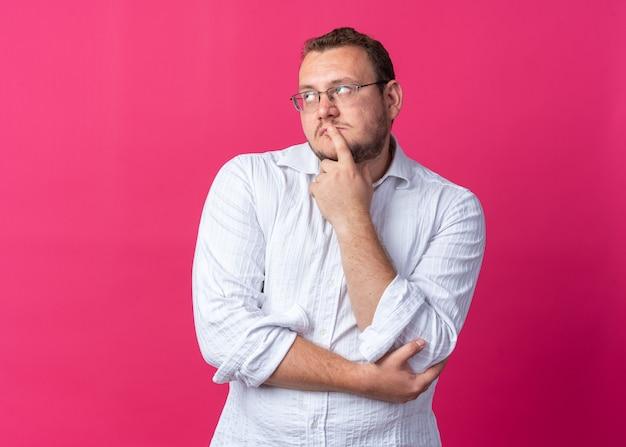 안경을 쓴 흰 셔츠를 입은 남자가 분홍색 위에 의아해 서 있는 모습을 올려다보고 있다