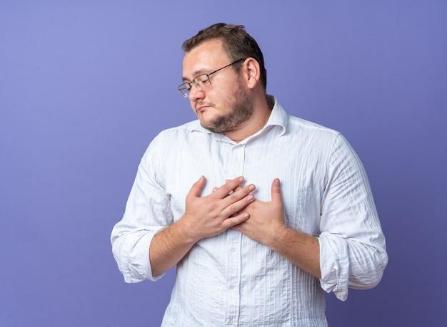 가슴에 손을 얹고 안경을 쓴 흰 셔츠를 입은 남자는 행복하고 긍정적인 느낌으로 파란 벽 위에 서 있는 것에 감사한다