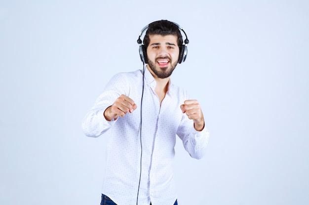 헤드폰을 착용하고 음악을 즐기는 흰 셔츠에 남자
