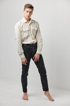 白いシャツの黒いズボンとポーズのファッションライフスタイルの男。高品質の写真