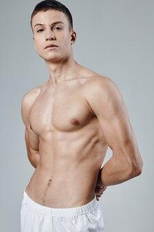 白いショートパンツの男は裸の胴体が筋肉を灰色に汲み上げた