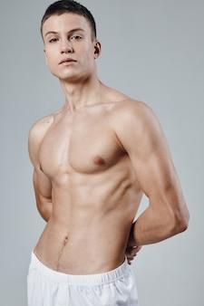 白いショートパンツの男は裸の胴体が筋肉をポンプでくみ上げた