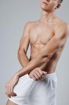 Человек в белых шортах тренировки накачал мотивацию тела обрезанный вид