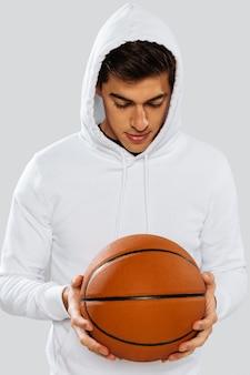 Человек в белой спортивной одежде играет в баскетбол