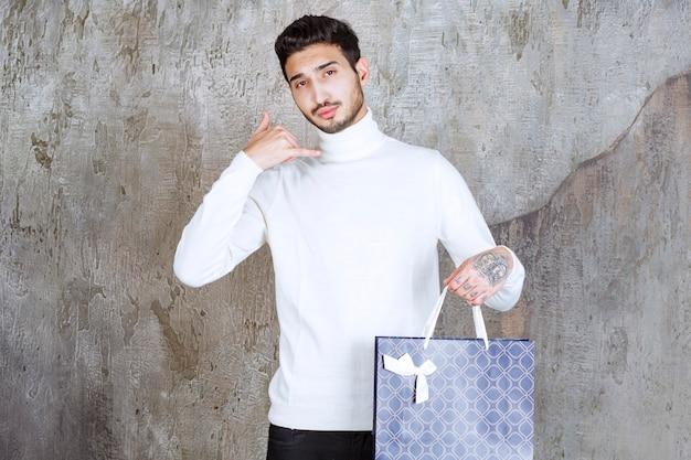 Человек в белом свитере держит синюю хозяйственную сумку и просит позвонить.