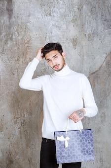 Человек в белом свитере держит синюю хозяйственную сумку и выглядит задумчивым.