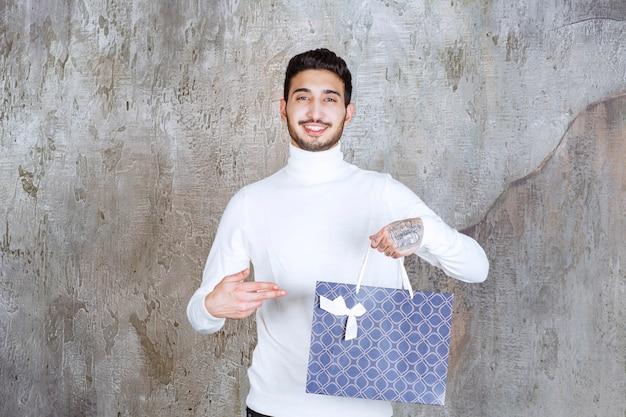 파란색 쇼핑백을 들고 흰색 스웨터에 남자.