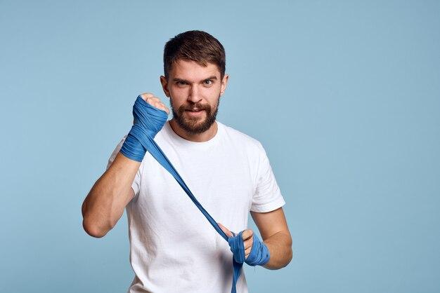 Человек в белой футболке и боксерских повязках на руках изолированы
