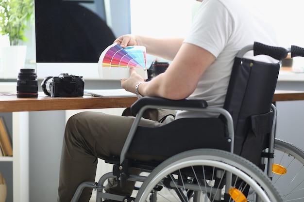 Мужчина в белой футболке и зеленых штанах сидит в инвалидной коляске и держит в руке разноцветную палитру.