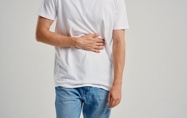 Человек в белой футболке и джинсах, касаясь его живота руками, боль в животе