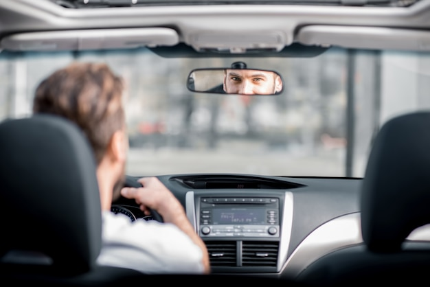 도시에서 차를 운전하는 흰색 티셔츠를 입은 남자. 거울에 반사된 뒷모습