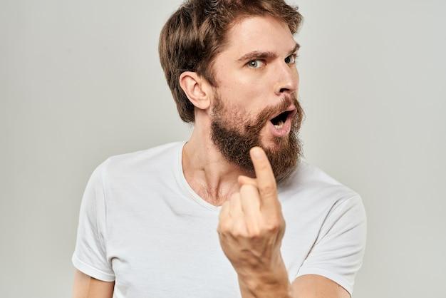 Человек в белой футболке эмоции выражает жест с руками обрезанный вид световой стены.