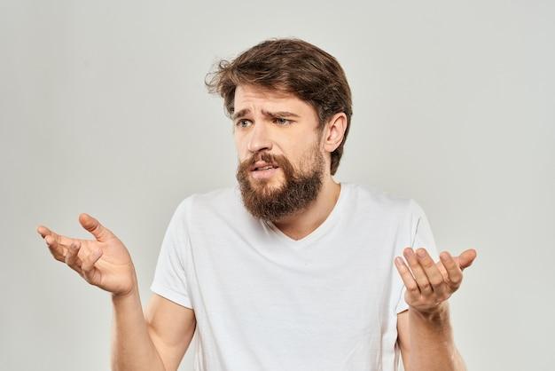 彼の手で身振りで示す白いtシャツの男スタジオ不満明るい背景