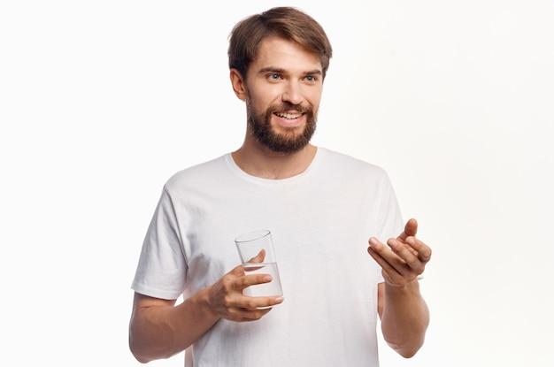 Человек в белой футболке стакан воды светлом фоне. фото высокого качества