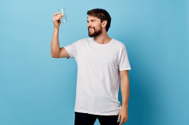 Человек в белой футболке стакан воды studio. фото высокого качества
