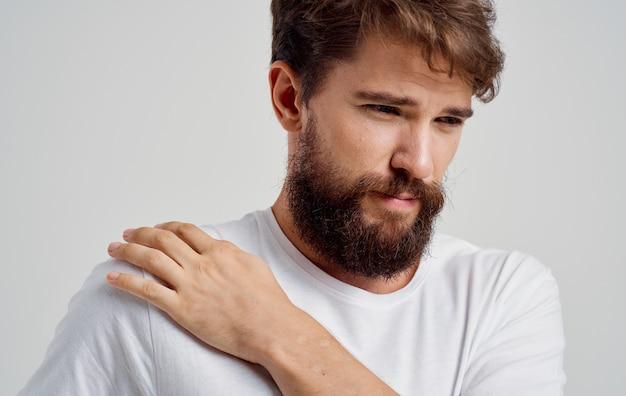 Человек в белой футболке страдает от боли