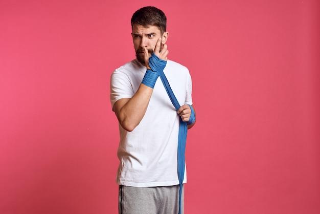 Человек в белой футболке связывает руку повязкой боевых искусств