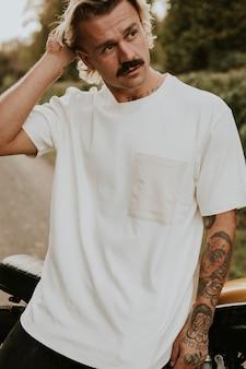 시골에 서 있는 디자인 공간이 있는 흰색 티셔츠를 입은 남자