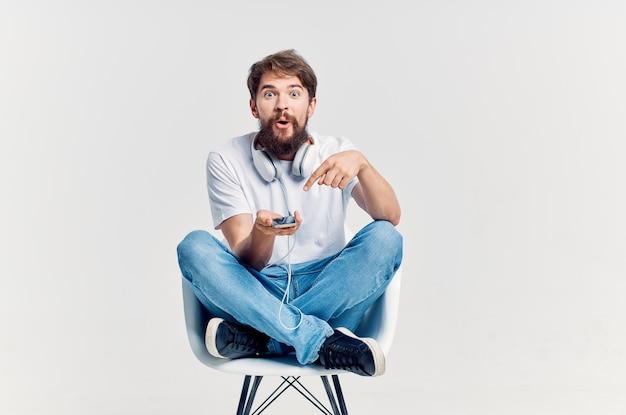 ヘッドフォンエンターテイメントで音楽を聴いている白いtシャツの男