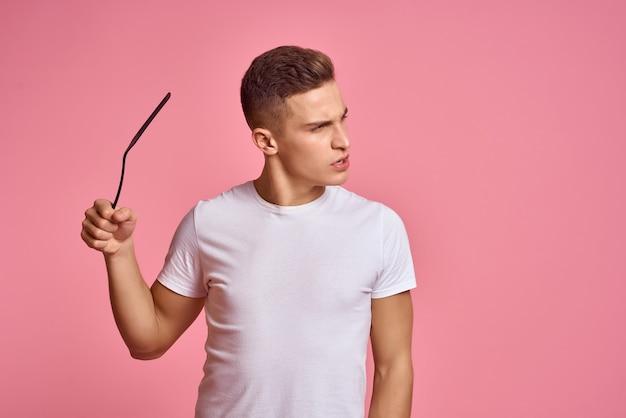 ホームスタジオで白いtシャツピンクの背景のリラクゼーションの男