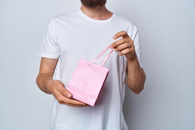 Мужчина в белой футболке с розовой упаковкой в подарок показывает еще один