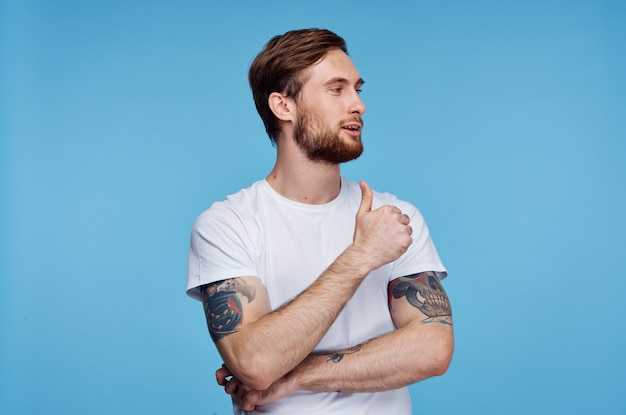 青い背景スタジオの親指を示す白いtシャツの男
