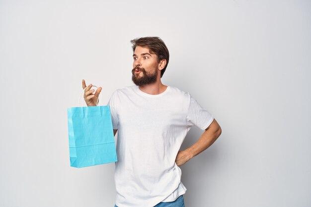 파란색 패키지 패션 쇼핑 판매 밝은 배경을 가진 흰색 티셔츠를 입은 남자