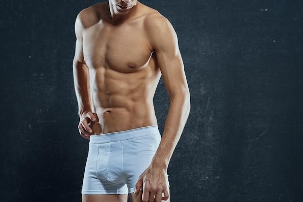 白いパンツの男は、ボディフィットネス運動ボディービルをポンプアップ