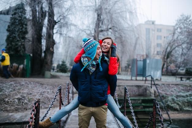 Человек в зимней одежде со своей подругой на спине