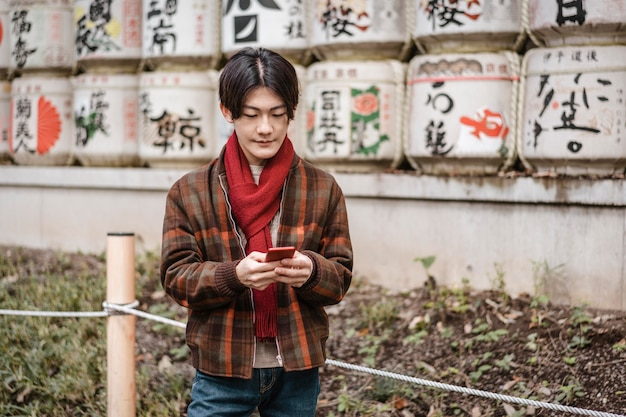 Человек в зимнем наряде с помощью смартфона на открытом воздухе