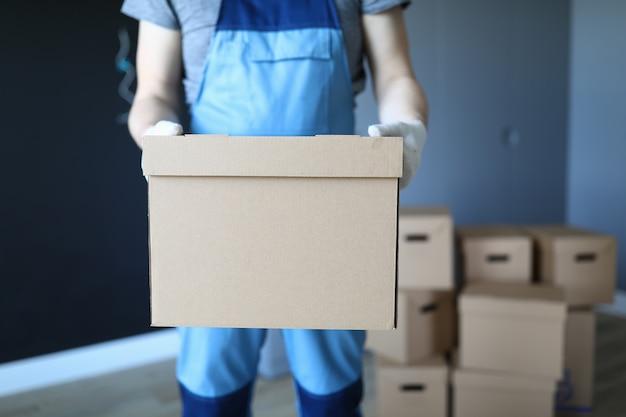 Человек в рабочей одежде стоит в офисе с коробкой