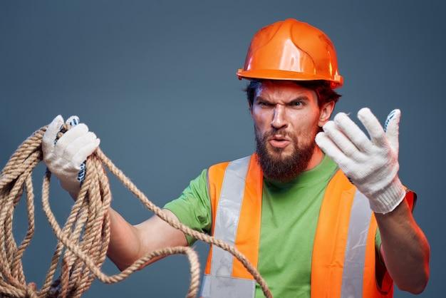 作業服の男制服オレンジ色のペンキロープを手にハードワークトリミングビュー。高品質の写真