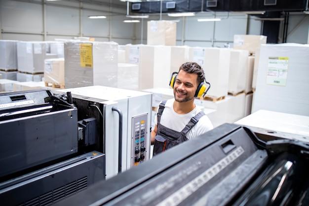 Человек в рабочей униформе работает печатной машиной в типографии с кучей листов на заднем плане