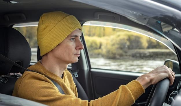 노란 모자와 스웨터를 입은 남자가 강과 아름다운 가을 숲을 따라 차를 운전하고 있습니다. 자연, 여행 및 가을 분위기의 개념