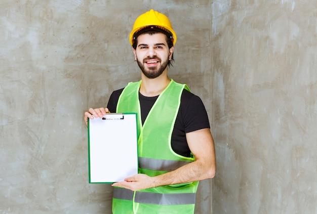 프로젝트 계획을 들고 긍정적으로 보이는 노란색 헬멧과 장비를 입은 남자