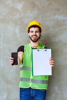 프로젝트 계획을 들고 전화기를 보여주는 노란색 헬멧과 장비를 입은 남자