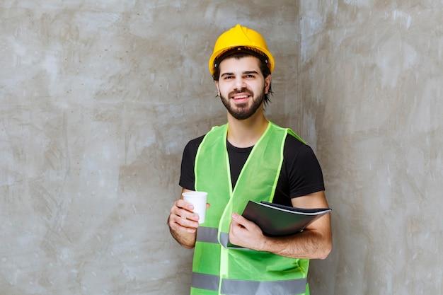 黄色いヘルメットと黒いレポートフォルダーと飲み物のカップを保持しているギアの男