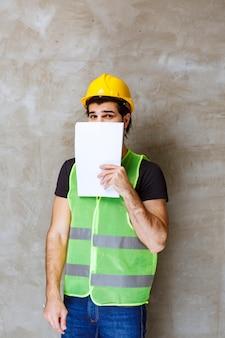 노란색 헬멧과 장비를 입은 남자가 프로젝트 보고서를 들고 그 뒤에 얼굴을 숨기고 있습니다.