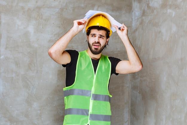 프로젝트 보고를 들고 노란색 헬멧과 장비를 입은 남자가 무섭고 겁에 질려 보입니다.