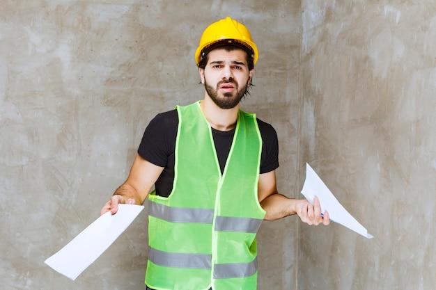 프로젝트 보고서를 들고 있는 노란색 헬멧과 장비를 입은 남자가 이에 대해 확신이 서지 않고 사려깊게 보입니다.