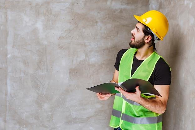 수리된 벽을 바라보며 만족감을 느끼는 노란색 헬멧과 장비를 입은 남자