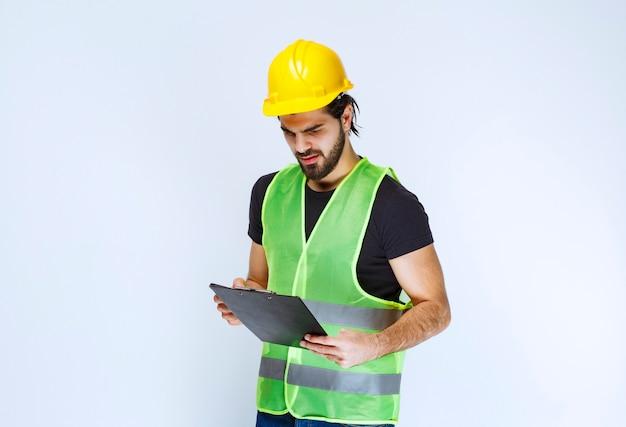 フォルダーのレポートをチェックする黄色いヘルメットの男。