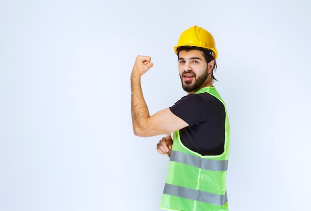 彼の腕の筋肉を示す黄色いヘルメットの男。