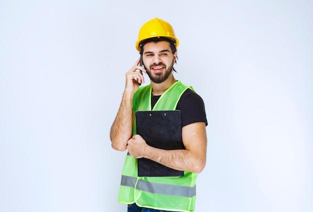電話に話している黄色いヘルメットの男。